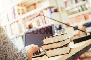 Learning for exams: Blonde female student in the university library, pile of books