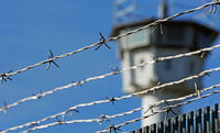 Barbed wire with a watchtower in the background