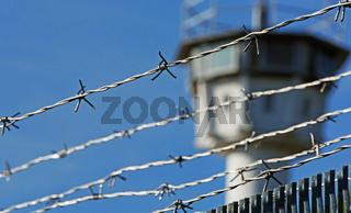 Stacheldraht mit Wachturm im Hintergrund