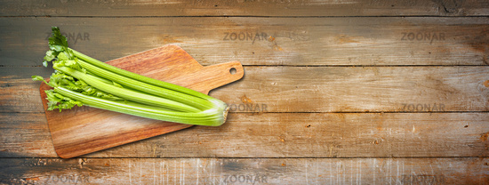 Celery branch bunch on a cutting board. Isolated on old wood banner background