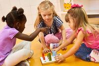 Drei Mädchen spielen zusammen ein Steckspiel
