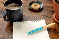 A blank notebook with a blue pen on a wooden desk, with a coffee mug