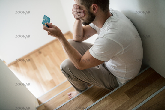 Depressed young man at home worried about finances