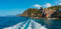 Beautiful summer Manarola coast view from excursion ship. One of five famous villages of Cinque Terre National Park in Liguria, Italy, suspended between Ligurian sea and land on sheer cliffs.