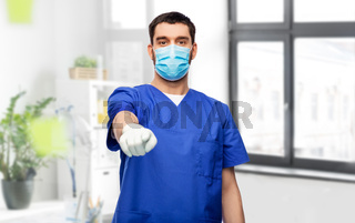 male doctor in blue scrubs and mask points finger