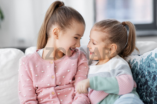 two happy smiling little girls or sisters at home