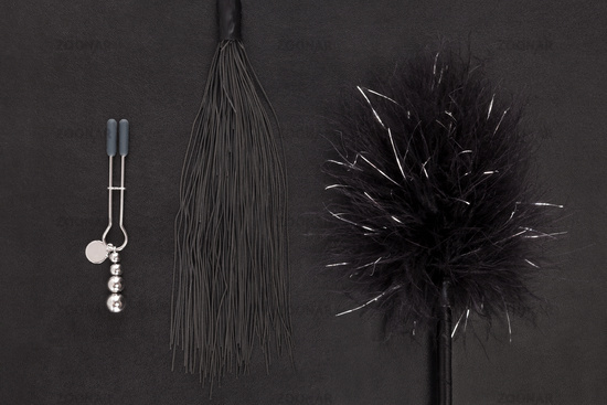 Kinky sex toys, whip, tickler and nipple clamps.