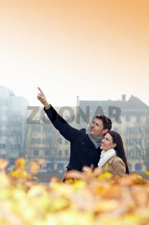 Mann in Stadt zeigt nach oben