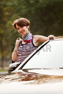 Happy young woman with a car