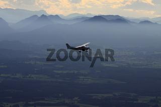 Sportflugzeug vor der Alpenkette