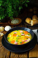 Hearty rustic pea soup with bacon and sausage