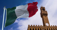 The Italian flag waving in the wind with the tower of Palazzo Vecchio in Florence in the background
