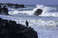 Two people stand hugging on the black lava coast and look at the stormy sea surf, Skardsvik, Iceland