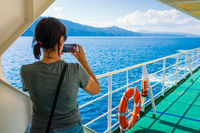 Woman tourist on the ferry on the way to vacation taking a photo with the phone - vacation, freedom concept