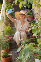 Beautiful female tourist wearing big straw sun hat and sundress sitting and relaxing on old stone house stairs during summer travel on Mediterranean cost on hot summer day and taking selfie