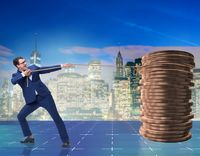 Businessman pulling stack of gold coins