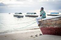 Young black man sitting on boat taking selfie