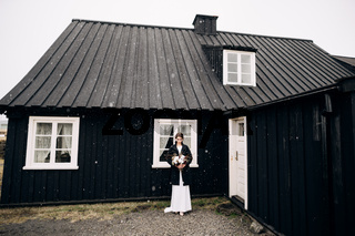 Portrait of a bride in a white silk wedding dress and a black coat with a bride's bouquet in her hands. Black wooden house with a white window. Snowing. Destination Iceland wedding.