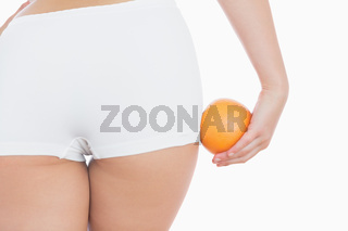 Woman in shorts with fresh orange