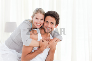 Lovely couple hugging on their bed