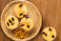 Top view of raisin sponge cupcake with pile of dried sweet raisin in bamboo tray .