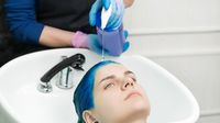 Hairstylist hands squeezes shampoo from tube into head woman with blue hair while washing hair in special sink at beauty salon