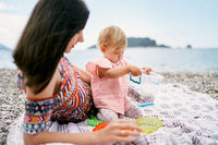 Mom lies on a blanket on a pebble beach next to a sitting little girl