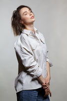 Portrait of young woman on gray background. Female posing in jeans, and milky white corduroy shirt.