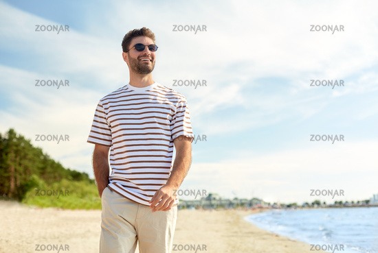 young man in sunglasses walking along summer beach