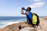 Fit afrcan american man wearing backpack resting drinking water on the coast