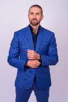 Portrait of handsome bald bearded businessman in suit