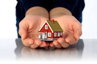 Hands and small house. Real estate or insurance concept.
