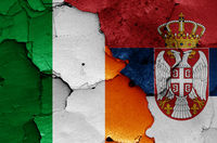 flags of Ireland and Serbia painted on cracked wall