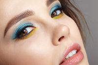 Closeup macro shot of  human female face with yellow liner and  blue eyes shadows.