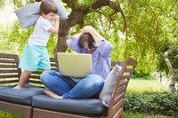 Sohn stört Mutter am Laptop mit Kissenschlacht