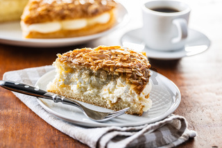Piece of sweet almond cake on plate. Pie with cream and almonds.