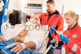 Sick patient with paramedic in ambulance treatment