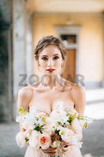 Portrait of the bride in a dress with a bouquet of pink flowers in the vaulted room. Lake Como, Italy