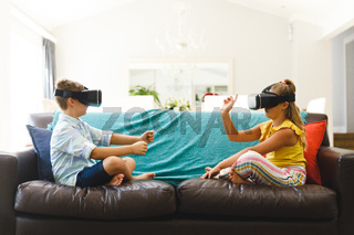 Caucasian brother and sister sitting on couch and using vr headsets in living room