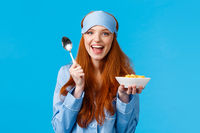 How about morning breakfast. Cheerful good-looking redhead female with excited expression, smiling eating cereals and holding spoon, standing blue background in nightwear, sleep mask