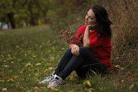 Beautiful thirty year old woman relaxes in the autumn park