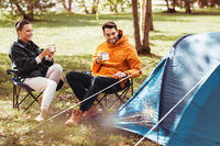 happy couple drinking tea at tent camp