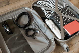 Open suitcase full of clothes isolated on wooden background
