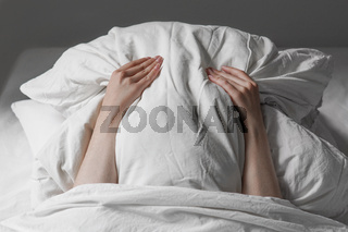 woman in bed hiding face under pillow