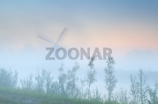 Dutch windmill in dense sunrise fog