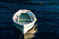 Fishing white wooden boat with oars on the blue water of the Bay of Kotor in Montenegro.
