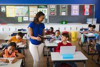 African american female teacher teaching caucasian boy to use digital tablet at elementary school