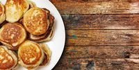 pile of freshly baked pancakes lay on a plate isolated on wooden table background.