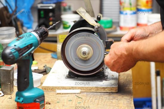 Detail of hands working on sharpening machine tool
