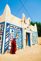 Exterior view to Dosso sultan residence and portrait of sultans guard in national uniform , Niger